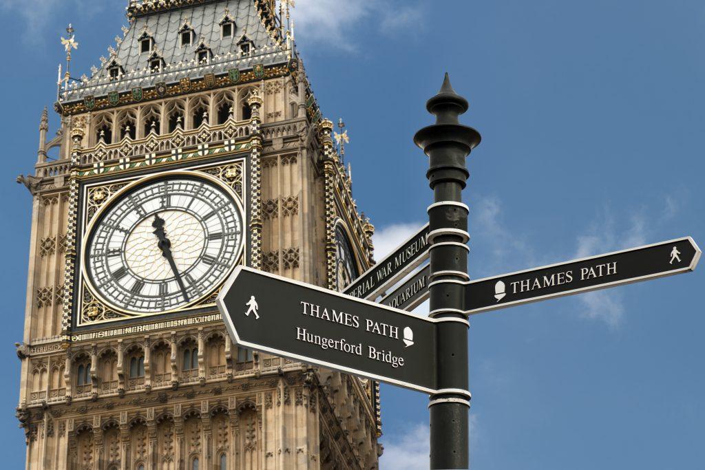 Big Ben over blue sky with pedestrian information sign.